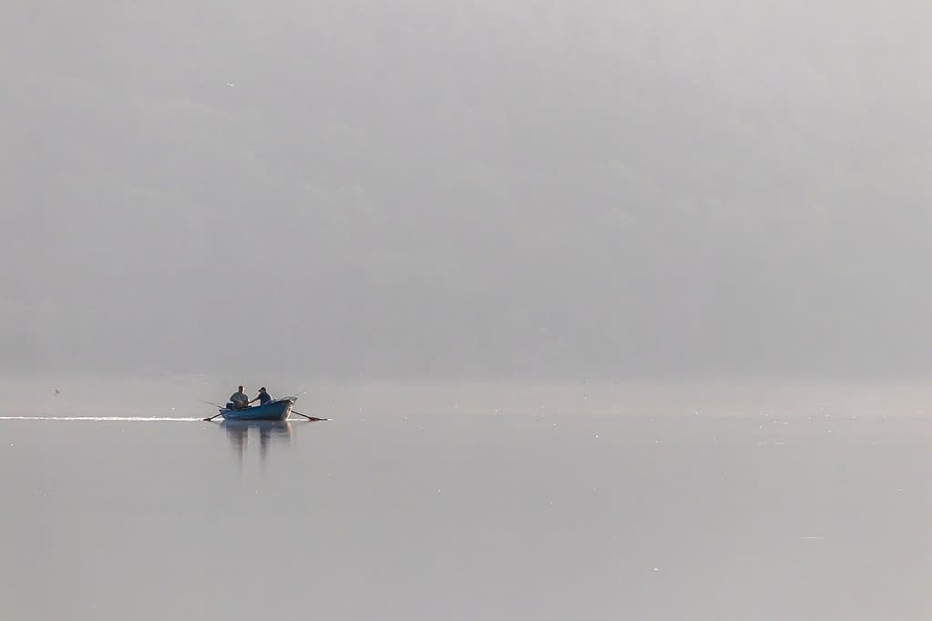 Boat on early morning lake representing the writer's journey